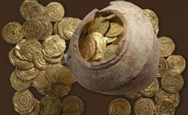 A 108 gold dinars and quarter dinars were found buried amidst a heavy quantity of sand in a ceramic jug. Image courtesy of the American Friends of Tel Aviv University