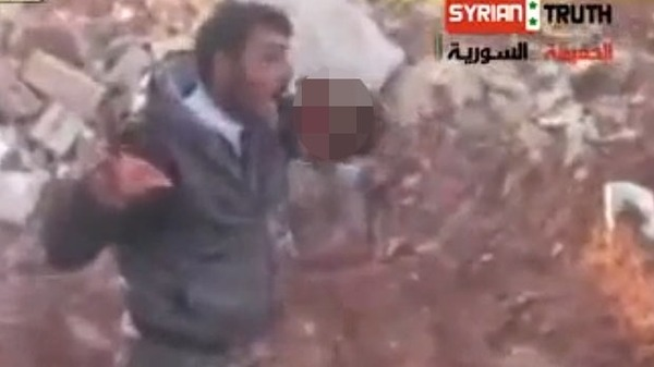 Screen shot of a Syrian rebel cutting out and eating the organs of a regime soldier. Al Arabyia