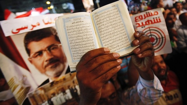 A copy of the Quran is held up near a poster of deposed Egyptian President Reuters