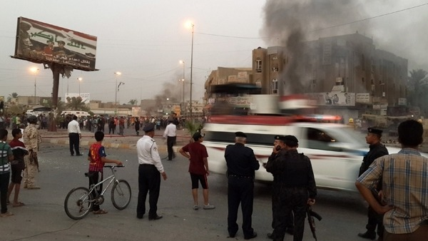 Iraqi policemen and people gather at the site of a car bomb AFP