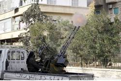 A fighter from the Al Qaeda-aligned Nusra Front fires a mounted machine gun - Reuters