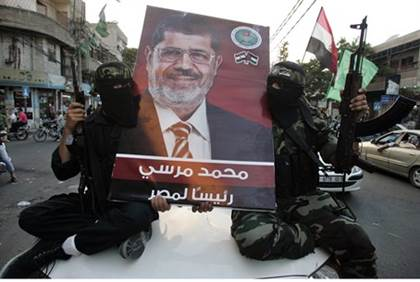 Hamas fighters hold picture of Mohammed Morsi